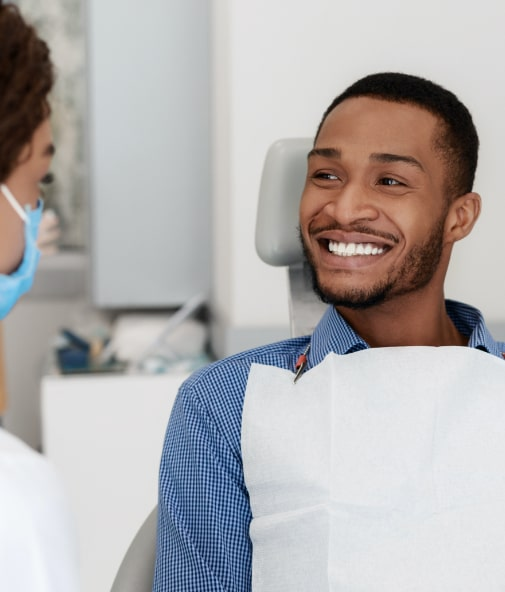 Female dental patient smiling and sitting back in chair