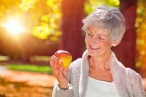 Smiling woman with apple and dentures in Los Gatos