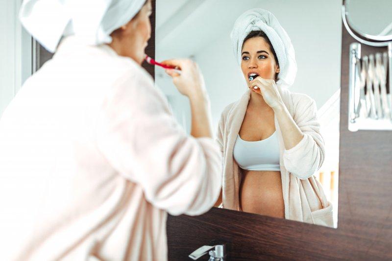 Pregnant woman brushing her teeth in bathroom