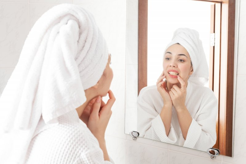 Woman checking her teeth and gums in mirror