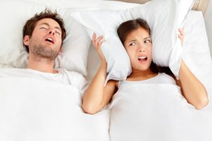 Man with sleep apnea snoring next to partner.