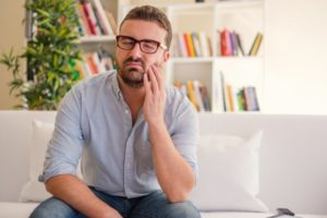 man holding his cheek in pain because he needs wisdom teeth removal